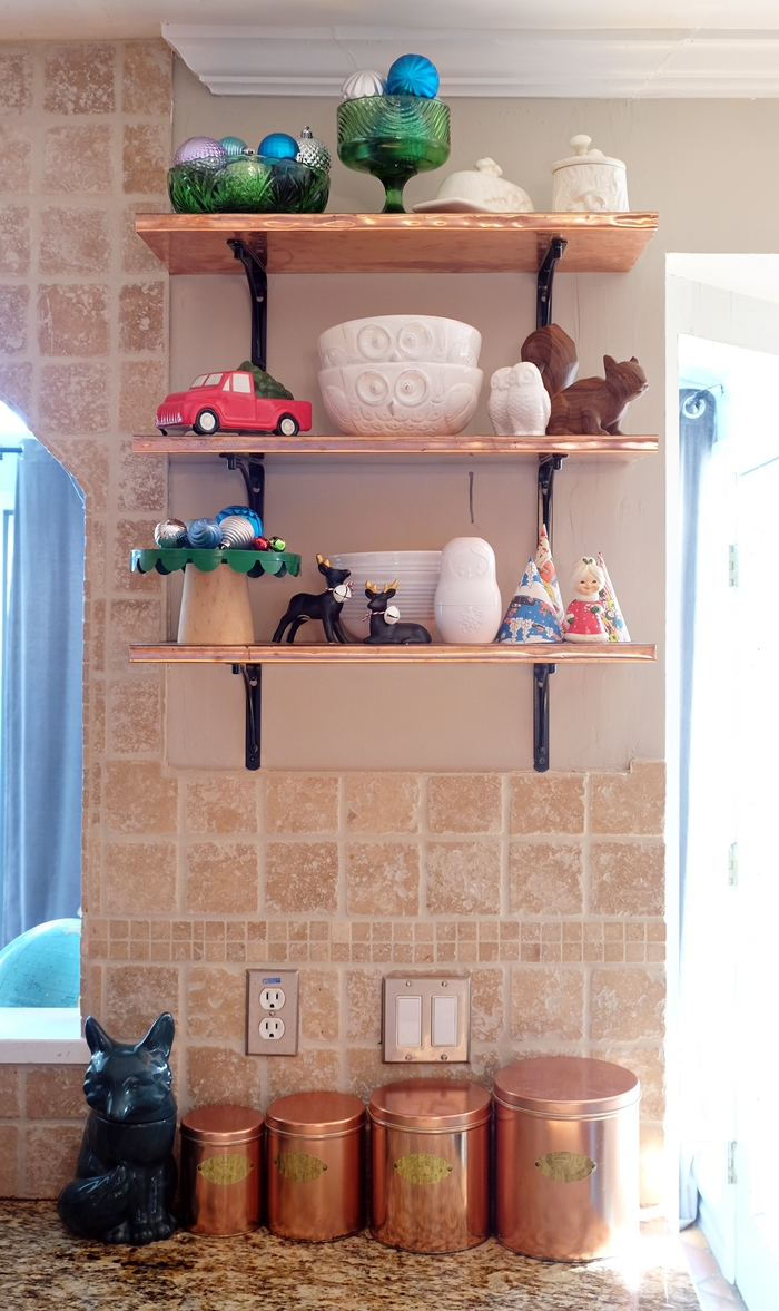 copper shelves with Christmas decorations in kitchen