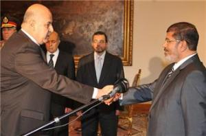 Mahmoud Mekki (left) shaking the hand of President Morsi (right)