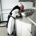 A trappist monk at the Spencer Brewery looks into a brew tank.