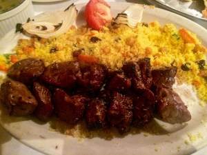 Lamb kabobs, couscous, a tomato on a plate.