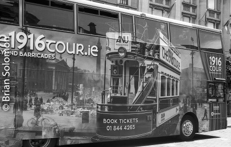 Dublin Bus on O'Connell Street in Dublin in September 2016. The tour bus is decorated with a collage of historic and modern images of Dublin trams.