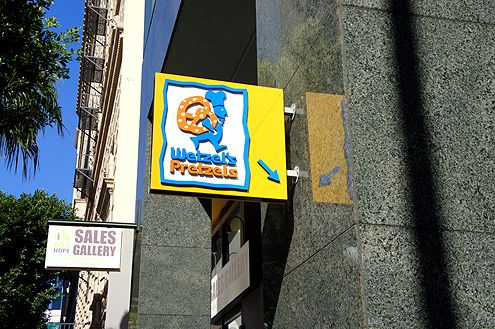 A new Wetzel's Pretzels sign points down toward the 7th/Metro subway station entrance where the new chain eatery is now open