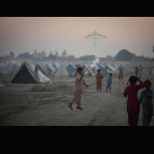 Pakistan,A boy flies a kite in a camp for people displaced by flooding