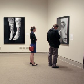 Visitors study Shirin Neshat's work in She Who Tells a Story