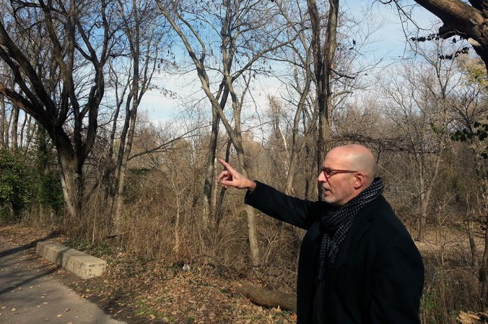 Architect Matthew Kuhl points to a landscape feature at the Waterfront Botanical Gardens site. (Elijah McKenzie / Broken Sidewalk)