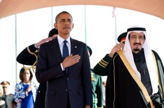 President Obama and King Salman Arabia stand at attention during the U.S. national anthem as the First Lady stands in the background with other officials on Jan. 27, 2015, at the start of Obama's State Visit to Saudi Arabia. (Official White House Photo by Pete Souza)