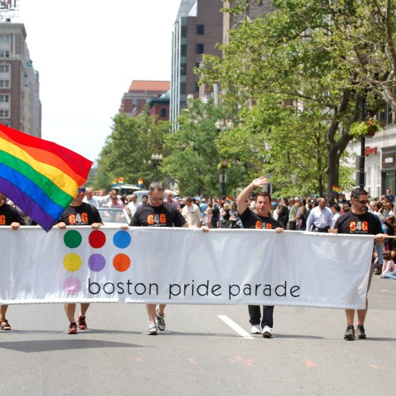 Participants march in the Boston Pride Parade Saturday afternoon, waving both the Rainbow Pride flag and the American flag