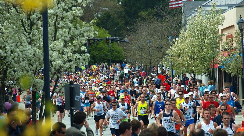 The 2010 Boston Marathon runners storm through Wellesley on their way to the Copley Square finish.  |  Photo courtesy of Wikimedia Common user Peter Farlow.