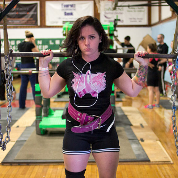 """You know what my squat would look like without a belt? It wouldn't,"" joked Kelly. Here she warms up for her squat."