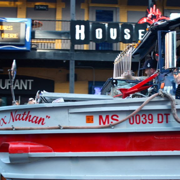 A player holds the World Series Trophy while riding in aptly named Duck Boat