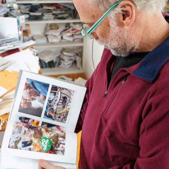 Touster examines a spread in his book featuring photos of the makeshift memorials that popped up in Copley Square just days after the 2013 Marathon bombings.