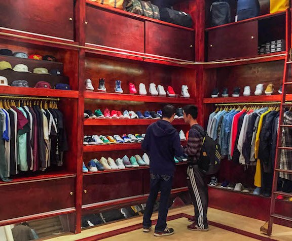 Two students browse through shelves of sneakers from Nike, Vans, New Balance and more.   Photo by Siena Tauber.