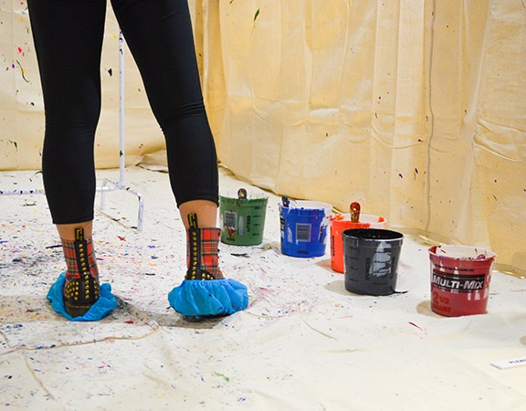 Eunie Jang protects her shoes while splatter painting.
