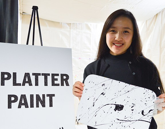 Eunie Jang holds up a finished laptop case after splatter painting it.