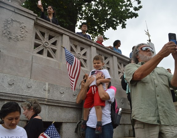 A woman lifts an american flag-clad child at the rally on the state house steps.