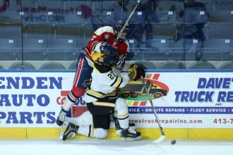 January 26,2018; Springfield, Massachusetts, United States; Robert Morris Colonials forward Michael Louria (7) is checked by AIC Yellow Jackets defenseman Janis Jaks (27) during a conference matchup between Robert Morris and AIC won by the Yellow Jackets 3-1 at the MassMutual Center. Photo: Brian Foley-Foley Photography.