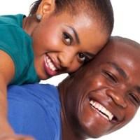young african woman enjoying piggyback ride on boyfriends back