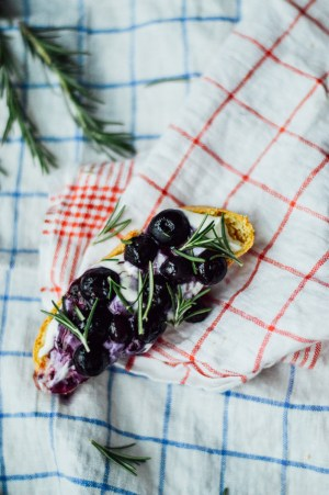 A deliciously easy Fourth of July Crostini recipe with roasted blueberries, whipped ricotta, honey, and rosemary / bygabriella.co @gabivalladares