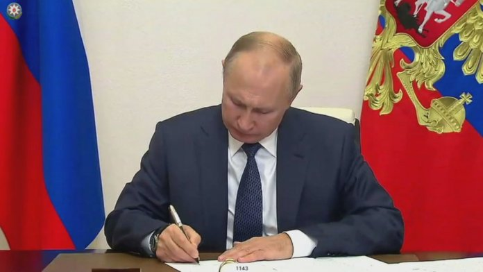 Russian President Vladimir Putin signing documents at Novo-Ogaryovo state residence, outside Moscow, Russia
