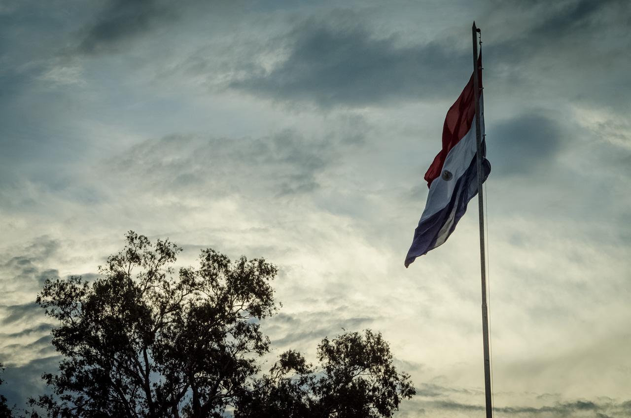 La bandera paraguaya flamea en el monumento erigido en el cruce de la ruta 2, en la localidad que todos conocemos como La Cruz del Peregrino. (Elton Núñez).