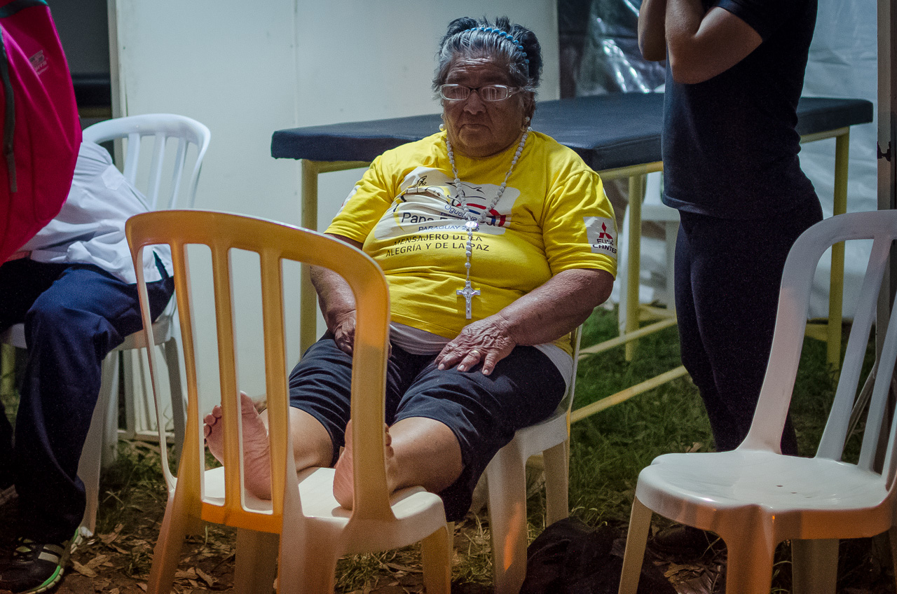 Una señora descansa sus pies en una de las carpas de servicios voluntarios al costado de la ruta 2, camino a Caacupé. En dicha carpa ofrecían agua, masajes y descanso a los peregrinantes. (Elton Núñez)