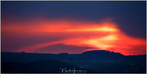 Hoog boven het land, boven op een heuveltop, zijn de grillige patronen in de lucht goed te zien. De plek waar de zon naar op weg is, verborgen achter donkere wolken