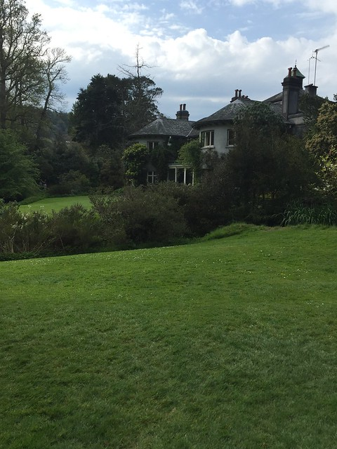 The house, quietly sitting in the centre of the gardens, with its sloping roofs and large baywindows