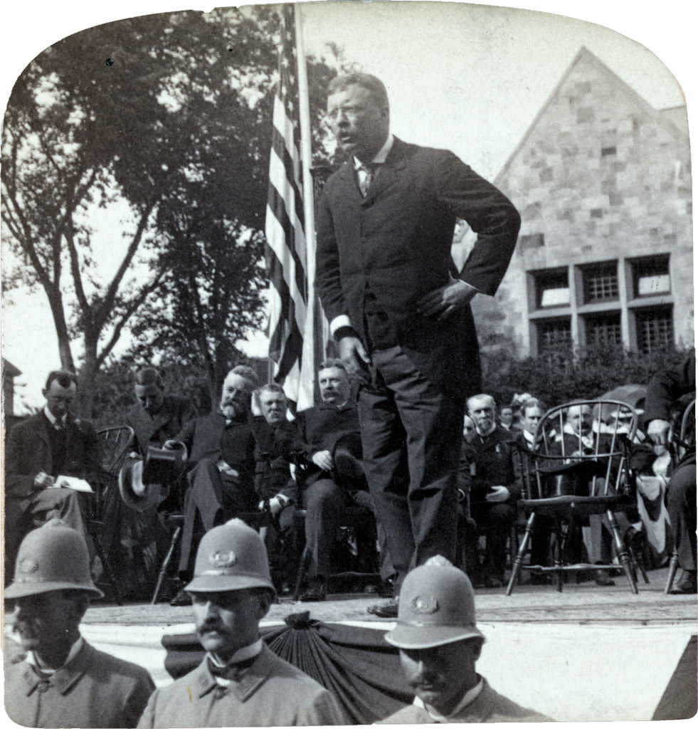 'The path of national greatness never is easy or smooth' - President Roosevelt, Nahant, Mass. 1902 image showing Teddy Roosevelt speaking on a platform with a group of people sitting behind him.