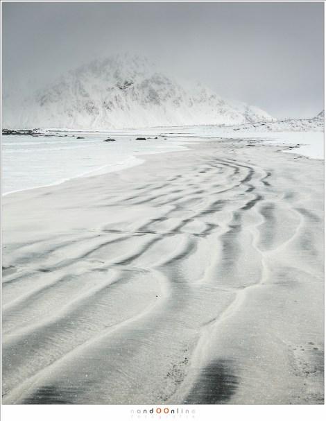 Het strand, vol met patronen van de branding, leidt de weg naar de berg op de horizon, half verborgen in de sneeuwbui die minuten later het strand bereikte