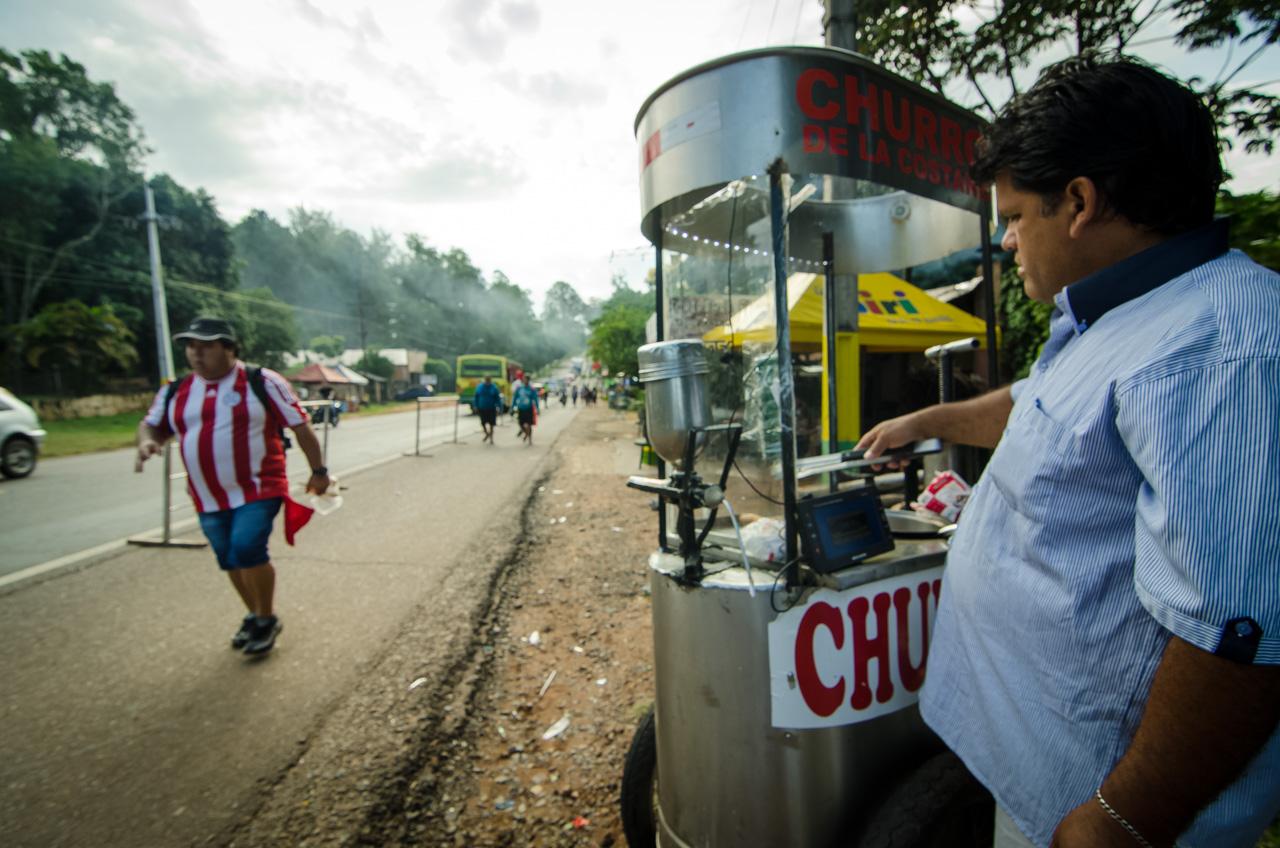 """Un vendedor ambulante prepara los """"churros"""" al costado de la ruta 2, preparándose para lo que será una tarde/noche bastante cargada de clientes. (Elton Núñez)."""
