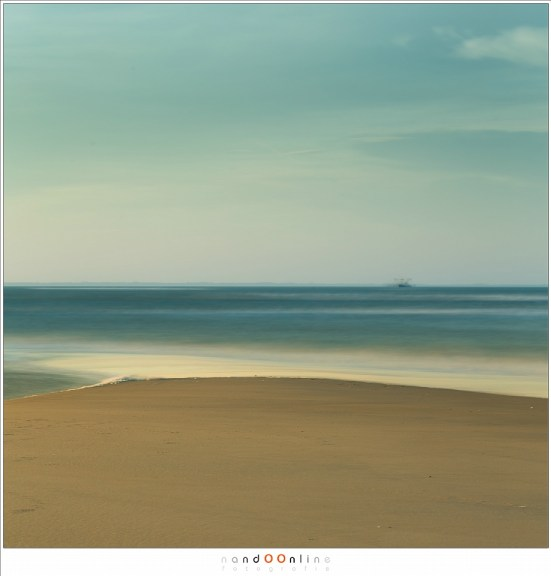 een zandbank die uitsteekt in de zee, met een vissersboot op de horizon