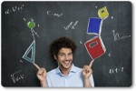 Portrait Of Happy Man Student With Books And Algebra Items Over A Blackboard