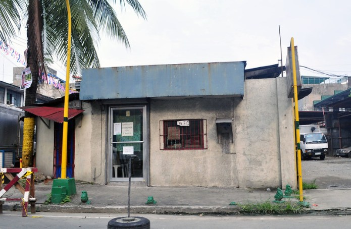 small office standing alone below a coconut tree