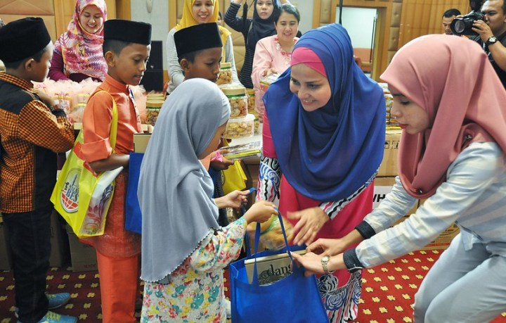 YBhg. Datin Seri Utama Datuk Anggraini Sentiyaki mengedarkan serunding dan kuih raya kepada kanak-kanak