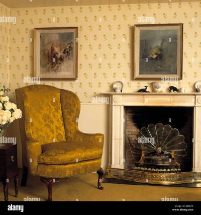 Gold brocade armchair beside fireplace with fan-shaped fireguard in Stock Photo: 570996 - Alamy