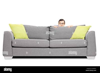 Frightened man hiding behind a sofa isolated on white background Stock Photo: 66356675 - Alamy
