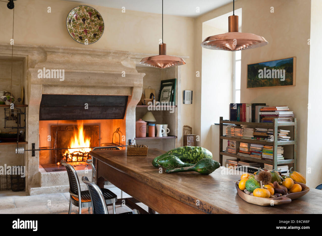 provencal kitchen with large stone fireplace and wooden dining table E4CW8F