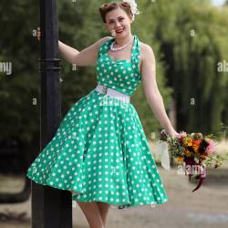 Woman in Vintage Polka Dot Dress Leaning From a Lamp Post Holding A