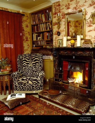 Tiger print wing chair and leopard print stool beside fireplace in Stock Photo, Royalty Free ...