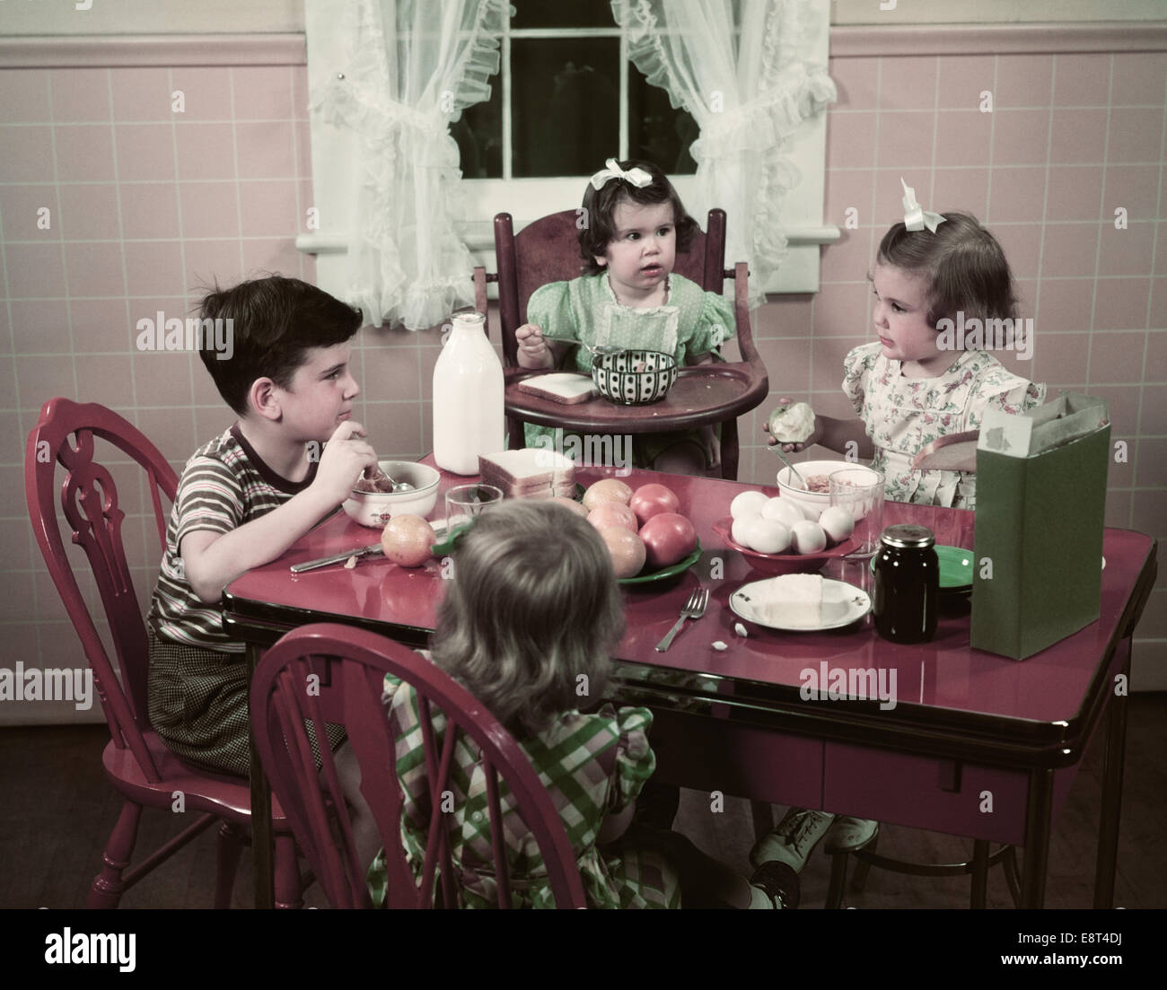 1940s 1950s boy and girls eating breakfast at kitchen table food cereal E8T4DJ