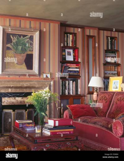Hardback books on coffee table beside fireplace and red sofa in Stock Photo, Royalty Free Image ...