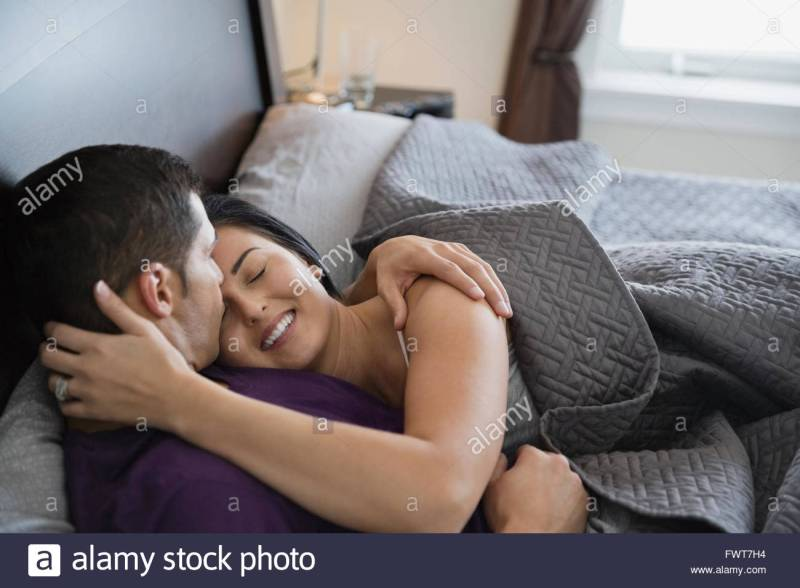 Romantic Couple Kissing And Embracing In Bed