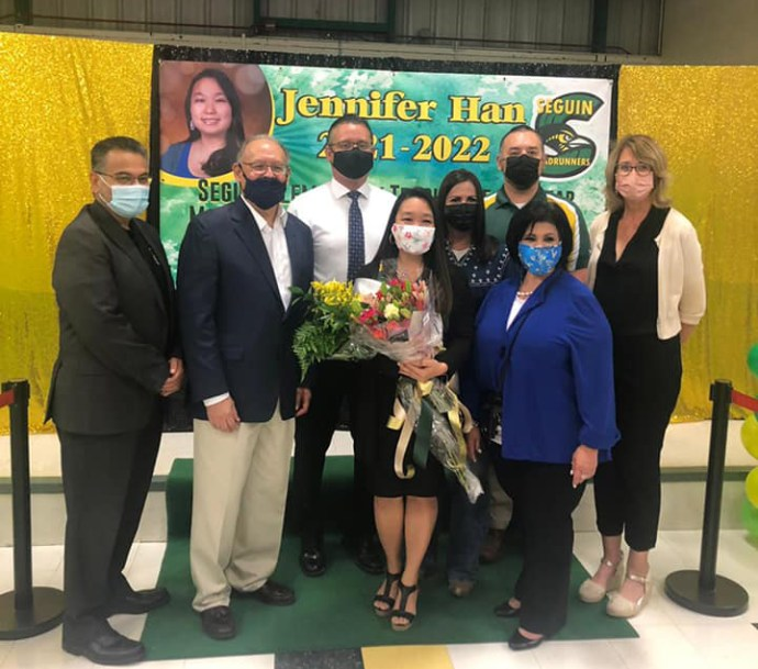 Jennifer Han戴着面具,手捧鲜花,在同事的陪同下参加学校的庆祝活动
