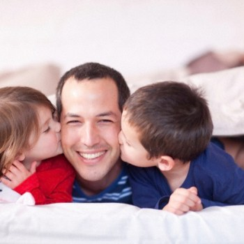 Son and daughter kissing fathers cheek under duvet --- Image by © Zero Creatives/Corbis