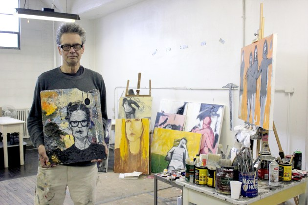 John W. Carlson holds his palette self-portrait standing inside his ArtCraft Building studio.