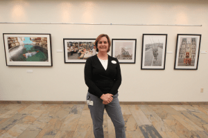"Deborah Bobrow, the Mandel JCC's arts and culture director, stands in front of photographer Scott Sill's exhibition, ""When You Travel You Are Never Lost,"" which showcased images from Sill's journeys through Asia and was on view in the JCC's hallways from July 11 to Sept. 5. Photo / Michael C. Butz"