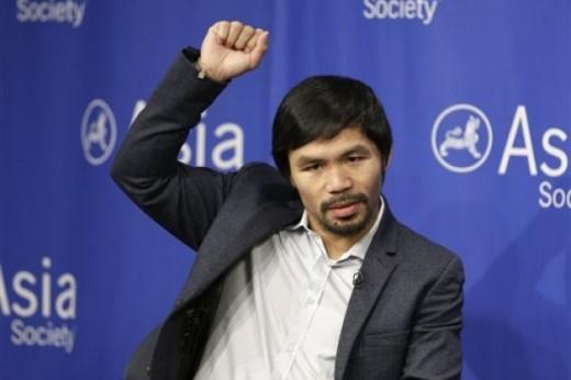 El boxeador filipino Manny Pacquiao muestra la movilidad de su brazo derecho, durante un acto de la Sociedad Asiática, el lunes 12 de octubre de 2015, en Nueva York. (AP ) -