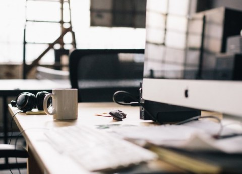 A creative desk, with an iMac and a coffee mug. SEO on Carinabehrens.com