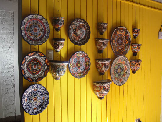 Talavera pottery pops against a yellow wall at Alter Eco