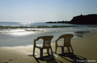 Chairs pulled up to the Pacific Ocean